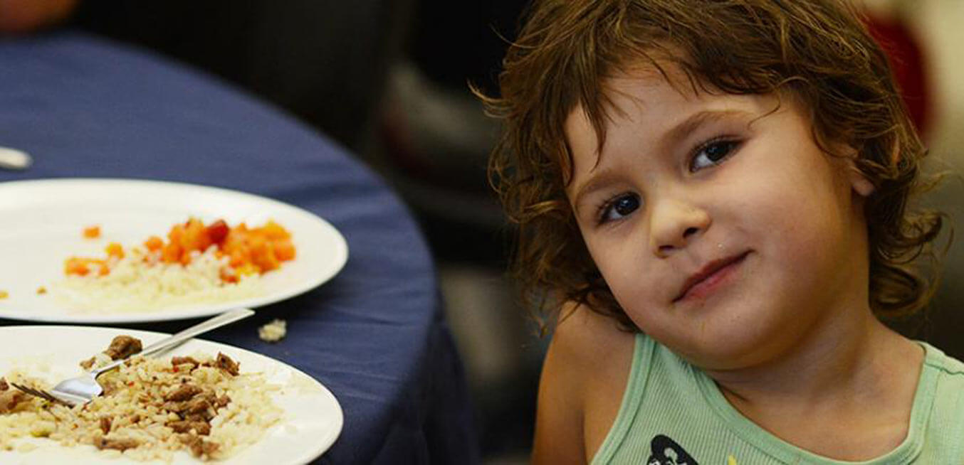 child with plate of food